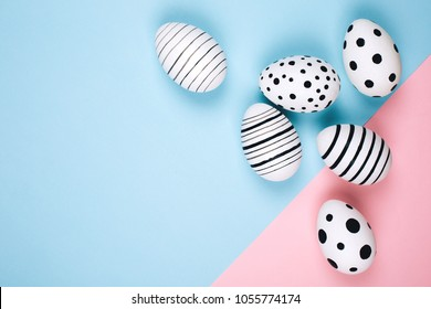 Many easter eggs on trendy pink pastel background. Eggs are hand-drawn. Flat lay style.