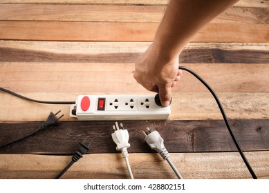 Many electrical plugs connected to a power strip or extension block on wooden table