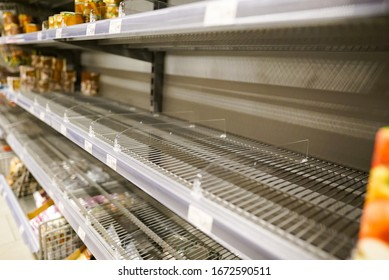 Many empty shelves with few canned goods left in a Eurpean supermarket because of panic shopping because of Covid-19 virus