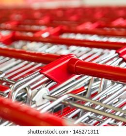 Many empty shopping carts in a row.