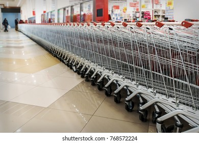 Many empty shopping carts in a row. Inside a large supermarket. Modern and stylish shopping Mall. Grocery store