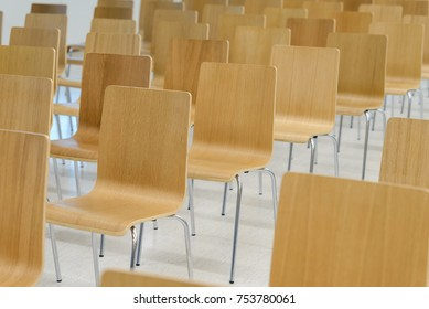 Many empty wooden chairs set neat rows in conference room
