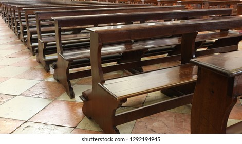 many empty wooden Church pew bench with kneeler inside a Christian church