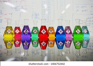 Many of Erlenmeyer flask with colorful liquid and Variety type of chemical hazard warning symbols labels on whiteboard with chemical learning background.
