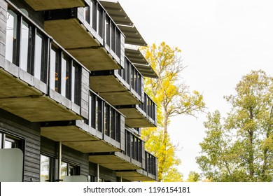 Many exterior black balconies on building from the side with autumn trees in the background.