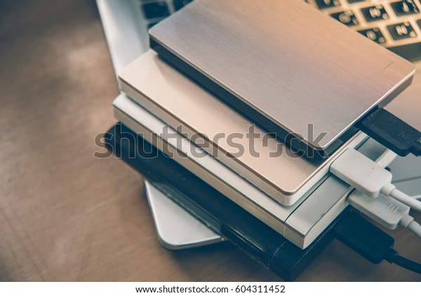 Many external hard disk on laptop  for backup files and important information using USB 3.0 connection, wooden table background.