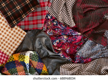 Many fabrics of different types. View from above. Fabrics in a cage, with a pattern, cotton, knitted mixed. Fabrics for sewing clothes and bed linen. Design of fabrics and fashion.