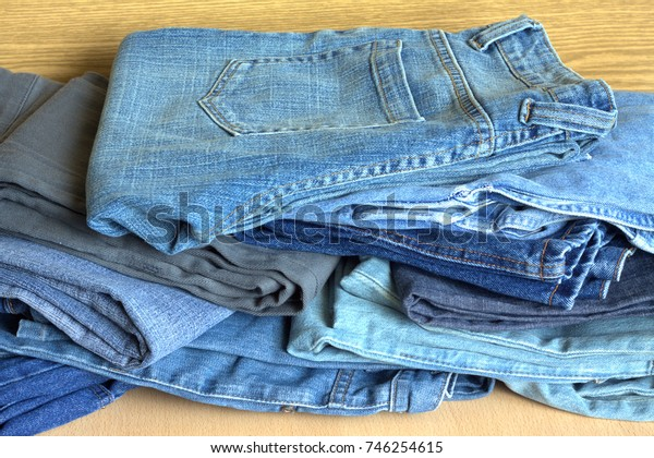 Many fashionable youth jeans lie in a mess on the wooden surface