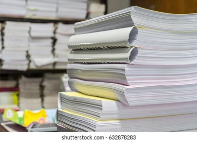 Many files and piles of paper lay on a messy office table at morning working day