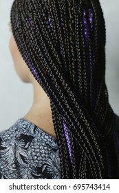 Many fine African braids are beautifully stylized in the hairdo,