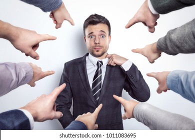 Many fingers pointing at a businessman