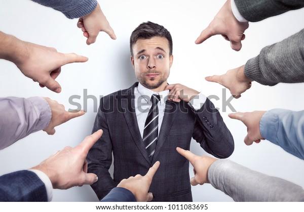 Viele Finger weisen auf einen Geschäftsmann hin