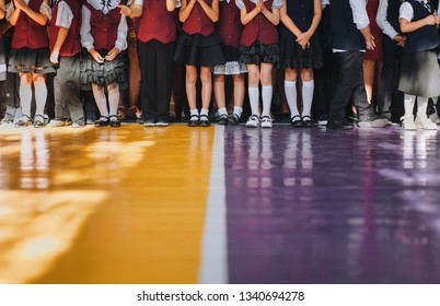 Many first-graders feet are on the yellow-purple floor. Beginning of the school year.