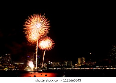 Many flashing fireworks with night cityscape background celebrate New Year.