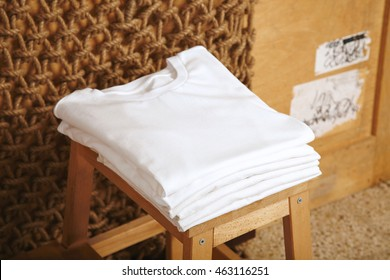 Many folded white basic cotton t-shirts presented in rustic interior