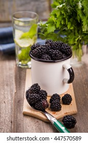 many fresh blackberry in white metallic old cup with lemon water