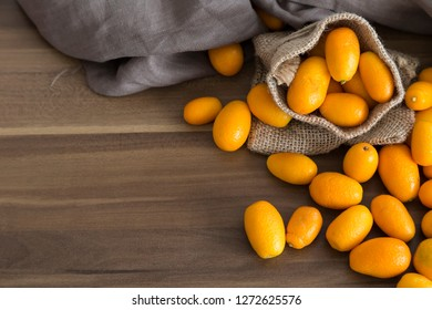 many fresh orange  kumquat a tropical fruit for sale at greengrocer store. Kumkuat and wicker bag from Turkey.