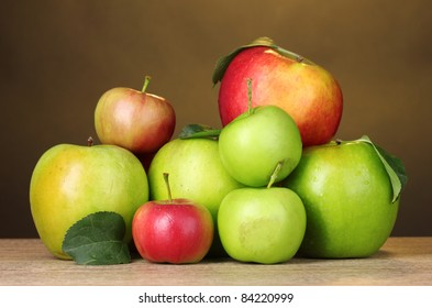 Many fresh organic apples on wooden table on yellow background