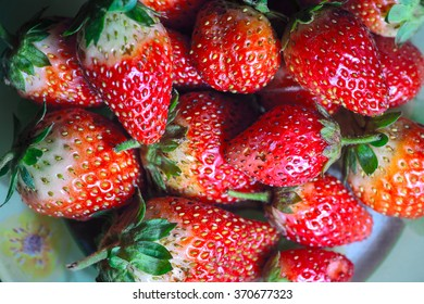 Many fresh strawberries on the plate.