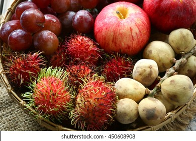 Many fruits in basket, apple, grape, rambutan, Wollongong on wood background
