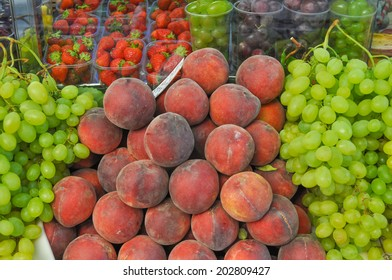 Many fruits including peach uve strawberry on a supermarket shelf