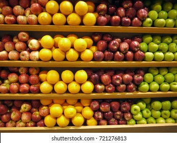 Many fruits on shelves at the supermarket,green and red apple,orange for sell.