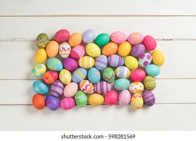 Many Fun and Colorful Dyed Easter Eggs Gathered in Center of Rustic White Board Background with room or space for copy, text, your words or design on top, sides or bottom of horizontal frame top view