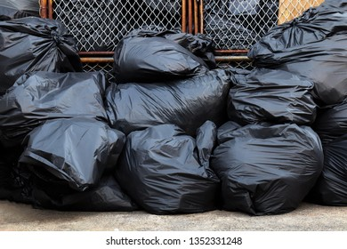 many garbage plastic bags black waste at litter area dump, garbage pile lots dump at wire mesh wall background, pollution from trash plastic waste garbage, bags bin of plastic waste, trash, 3r
