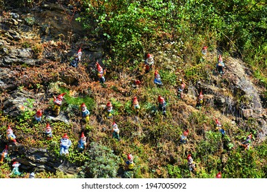 Many garden gnomes scattered on a meadow