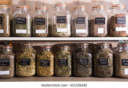 Many glass cans with different dried herbs standing on shelf in food store
