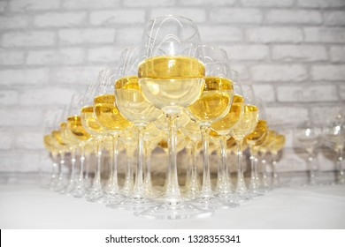 many glass goblets with white wine and champagne on the table