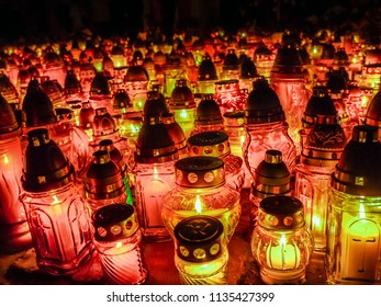Many glass votive candles lit in the dark