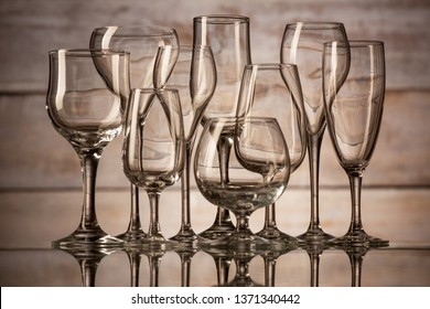 many glasses of different shapes on a wooden background