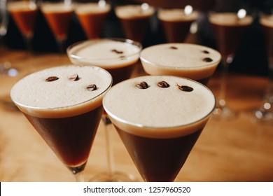 many Glasses of Espresso Martini Cocktail, vodka, kahlua, espresso coffee, in a Martini glass on wooden table. Vertical image.