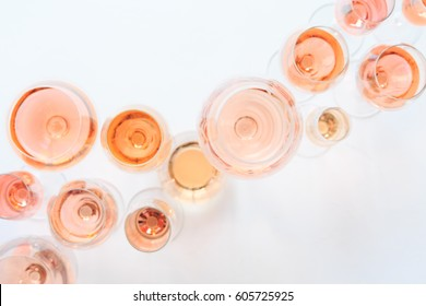 Many glasses of rose wine at wine tasting. Concept of rose wine and variety. White background. Top view, flat lay design. Natural light. Living Coral Pantone color of the year 2019 shade