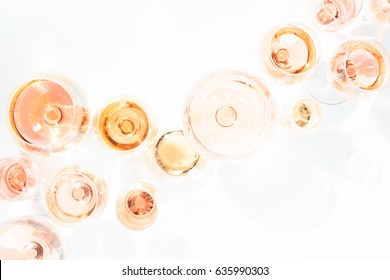Many glasses of rose wine at wine tasting. Concept of rose wine and variety. White background. Top view, flat lay design. Toned  overlight image. Horizontal