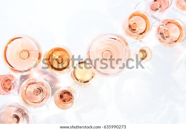 Многие бокалы розового вина на дегустации вин. Концепция розового вина и сорта. Белый фон. Вид сверху, плоский дизайн. Горизонтальная. Живой Коралл Pantone цвет года 2019 оттенок