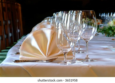 many glasses and yellow snapkins on decorated table