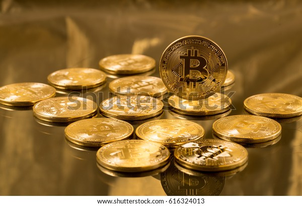 Many gold bitcoins laying on reflective surface with a single bitcoin in sharp focus floating above them to illustrate bitcoin exchange, mining or blockchain technology for cryptocurrency