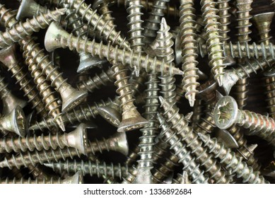 Many gold screws. Abstract background - macro photo.