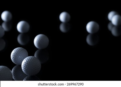 Many golf balls isolated on black background with empty copy space for text.