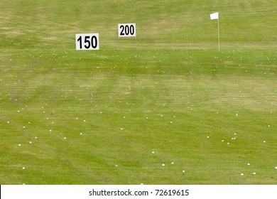 Many golf balls on fresh green with flag pole and distance signs