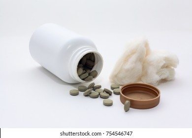 many green alfalfa tablet outside white bottle with isolated background