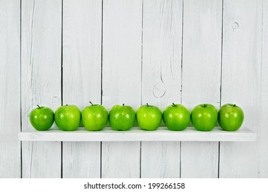 Many green apples on a shelf. A white, wooden background.
