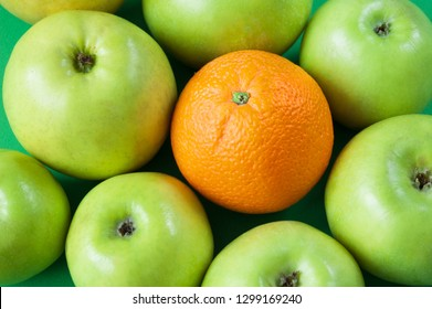 many green apples and one orange, concept