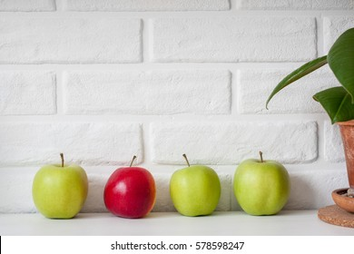 Many green healthy fresh apples and one red apple are put in line against white brick wall background. Healthy lifestyle. Diet or weight losing concept. Sport style of life. Scandinavian organic food.