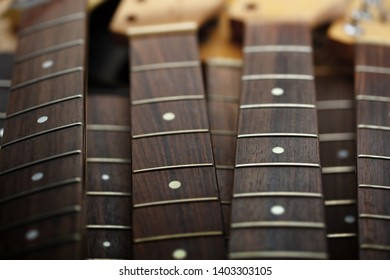 Many guitar necks aligned. Rosewood and ebony finger board electric guitar necks made from maple.