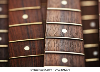 Many guitar necks aligned. Rosewood and ebony finger board electric guitar necks.