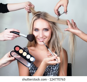 many hands applying make up on a woman head