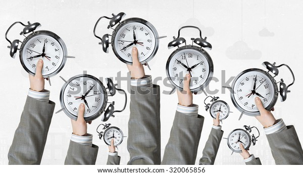 Many hands of business people holding alarm clock